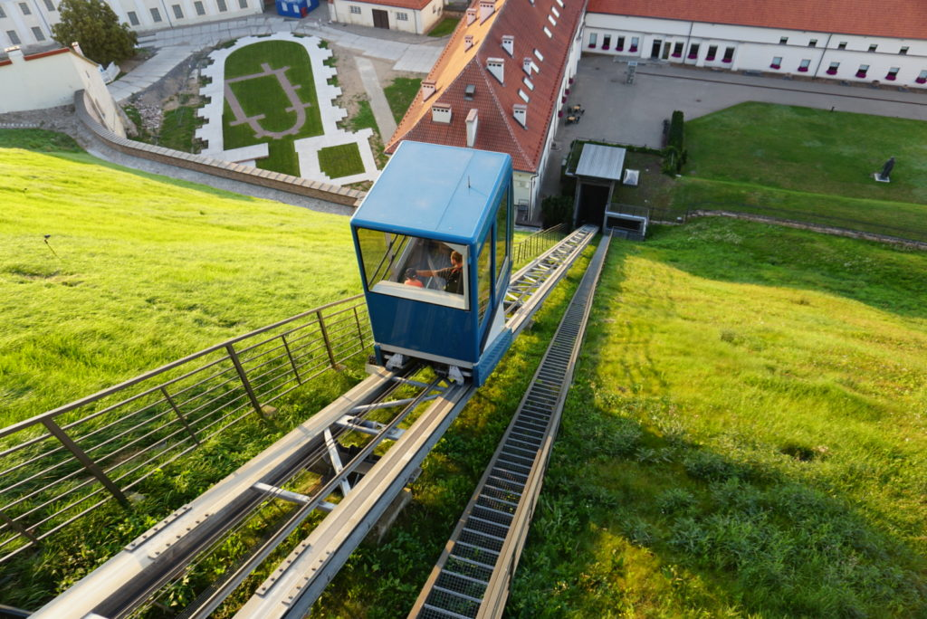 Blick von oben des Berges auf die Talstation des Schrägaufzugs. Eine kleine blaue Kabine die auf zwei Schienen mit einem Seil hochgezogen wird.