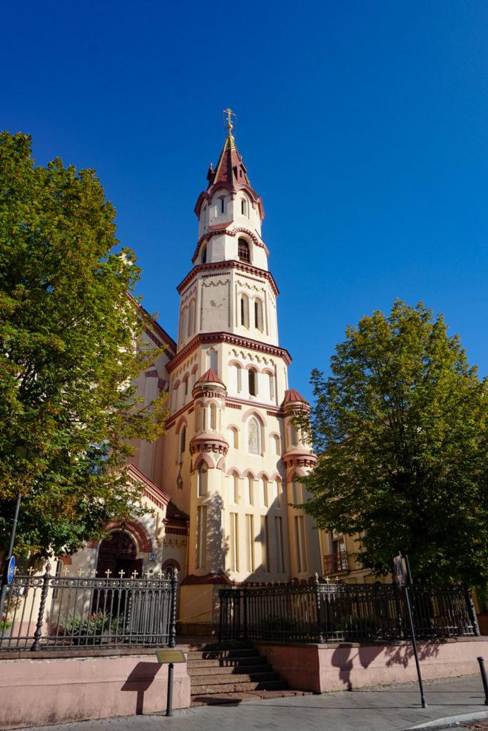 Die St. Nicolas Kirche von Vilnius. Eine gelbe Kirche mit einem großen Kirchturm. Dieser sieht wie übereinandergestapelte Bausteine aus.