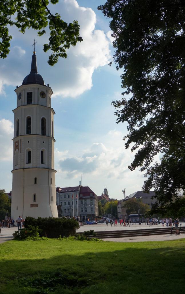 Der Glockenturm in Vilnius. Ein weißer großer Turm. An einer Stelle ist das Mauerwerk zu sehen, da war früher die Stadtmauer befestigt. Der Turm hat insgesamt 5 Etagen. An den Unteren beiden sind kleine Fenster, oben große.