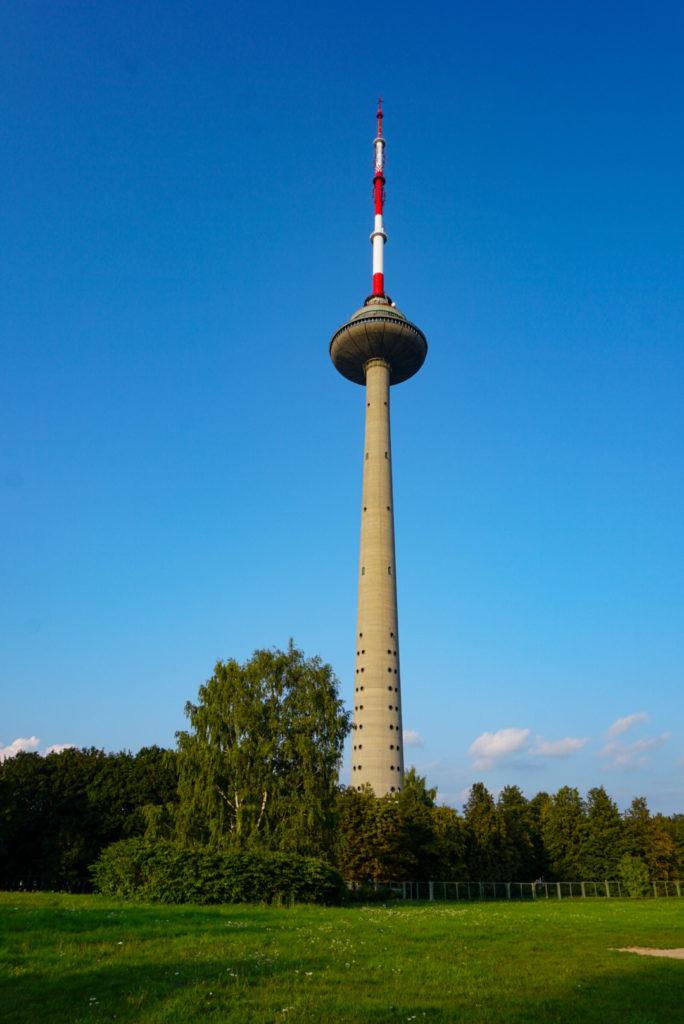 Der alte Fernsehturm von Vilnius. Vor dem Fernsehturm ist eine Wiese und viele Bäume. Der Turm selber ist aus Beton und wenig Farbenfroh. Die Spitze ist rot weiß gestreift.