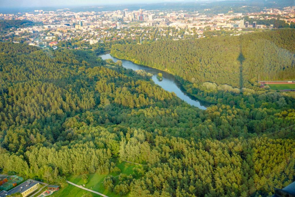Blick vom Fernsehturm über die Wälder und das dahinterliegende Vilnius. Ein Fluss teilt den Wald in zwei Teile. Der Schatten des Fernsehturms ist rechts im Bild auf dem Wald zu sehen.