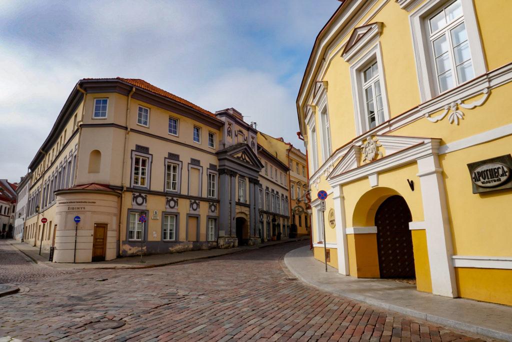 Eine Straßenecke in Vilnius. Die Straße besteht aus Kopfsteinpflaster und die Gassen sind eng. Rechts steht ein gelbes Haus mit schicken Verzierungen.