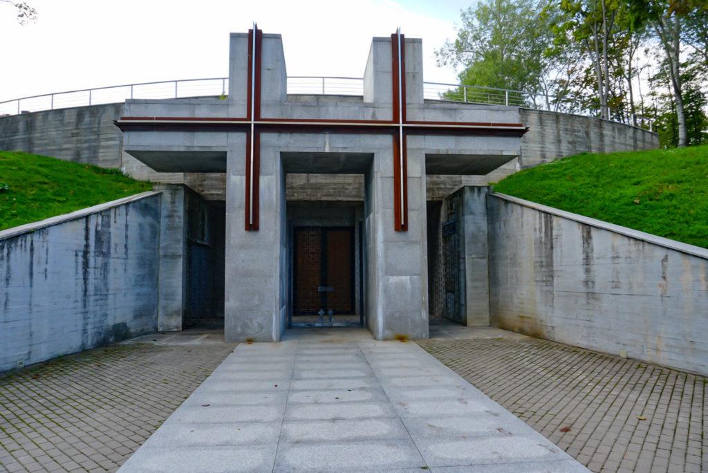 Der Eingang zur Kapelle. Dieser Betonbau wirkt nicht wie eine Kapelle. Im Vordergrund, als Eingang, steht eine Skulptur, die wie zwei aneinander gestellte Kreuze aussieht.