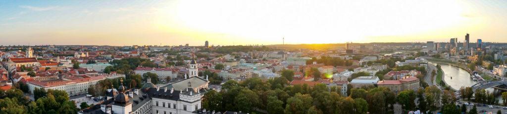 Blick auf Vilnius vom Gediminas Turm. Die Sonne steht leicht mittig des Panoramabildes. Überall ragen Kirchturmspitzen hervor. Rechts am Bild Rand fließt der Fluss Neris.