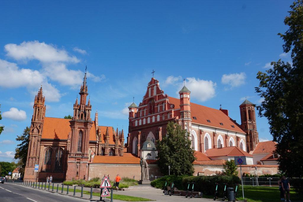 Zu sehen sind zwei alte Kirchen in Vilnius. Zwei sind aus Backsteinen gebaut, wobei die hintere größer ist. Rechts steht eine etwas neuere Kirche.
