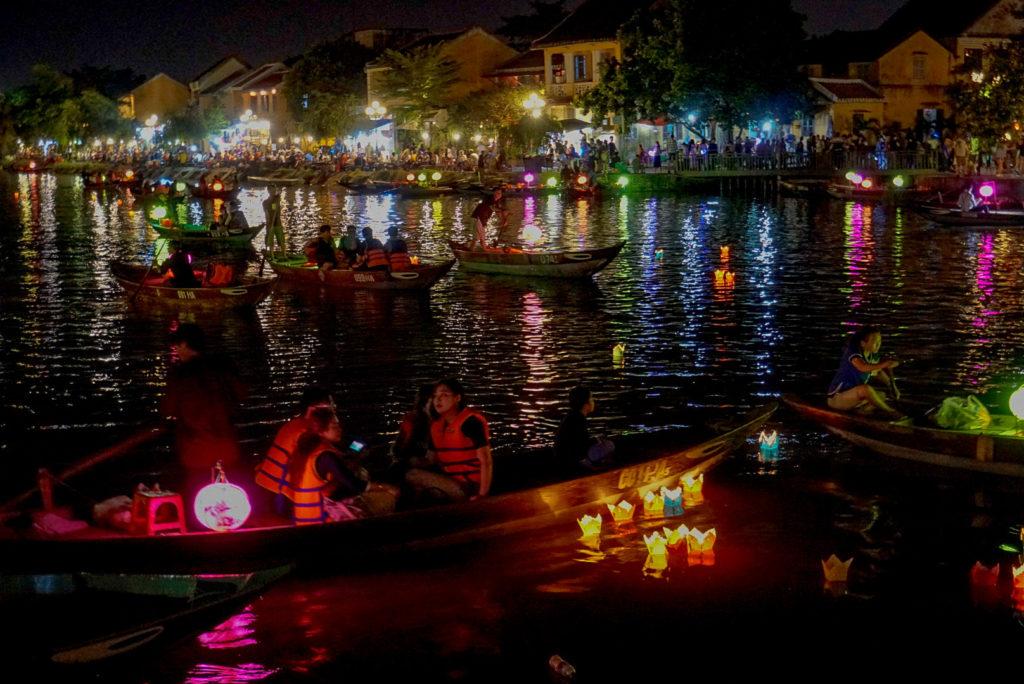 Eine abendliche Szene in Hoi An. Auf dem Fluss befinden sich viele Menschen, um sich in einem kleinen Boot rumfahren zu lassen. Einige haben auf dem Fluss Kerzen in Papierbehältern niedergelassen. An dem Rand des Flusses befinden sich viele bunt beleuchtete Restaurants.