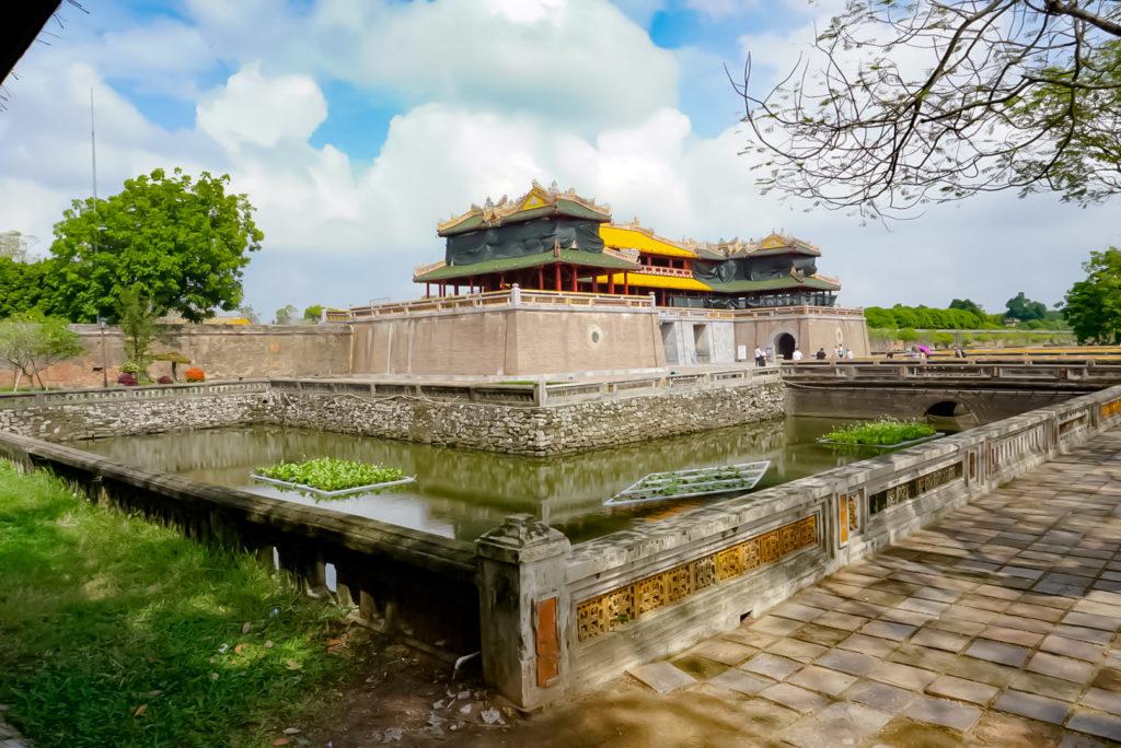 Die Zitadelle von Hue. Blick von einem der Teiche am Eingang auf den großen Platz. Die Dächer des Einganges sind in zwei Farben gehalten. Links und Rechts grün in der Mitte gelb.