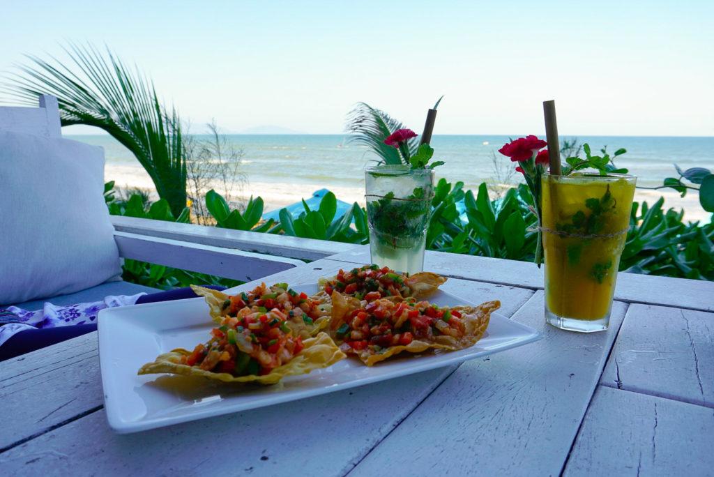 Das Foto wurde in einer Strandbar aufgenommen. Wir haben kleine vietnamesische Snacks bestellt sowie zwei Cocktails. Die Strohhalme sind aus nachhaltigem Bambus. Wir sitzen am Rand und haben Blick auf den Strand.