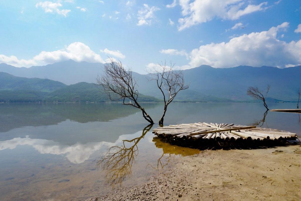 Ein typisches Postkartenmotiv. Stopp an einem See mit Bergen im Hintergrund. Im Vordergrund stehen zwei Bäume, die kahl sind. Davor ist aus Holz ein Floss gebaut.