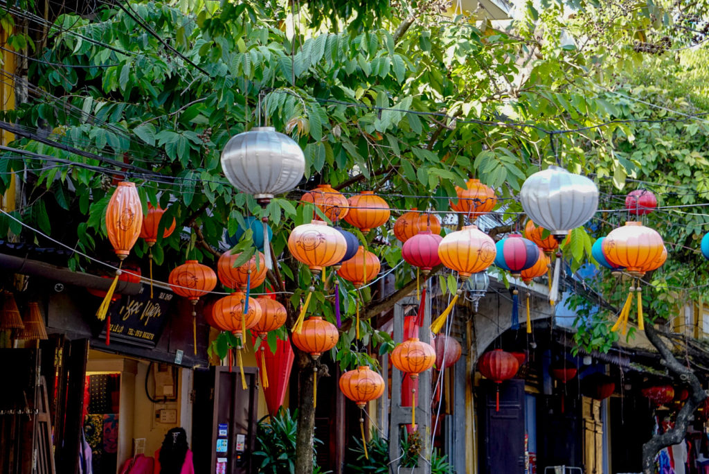Zwischen zwei Häuserreihen sind Stromkabel gespannt. An diesen hängen verschiedene Lampions. Sie sind weiß, orange oder rot. Dementsprechend ist es ein schönes Zusammenspiel zwischen den Bäumen und den Lampions.