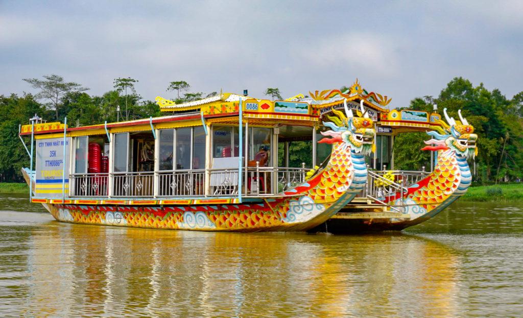 Ein großes Boot, auch Drachenboot genannt. Vorne am Boot sind zwei Drachenköpfe abgebildet. Es ist sehr bunt. Es fährt auf dem Fluss in Hue.