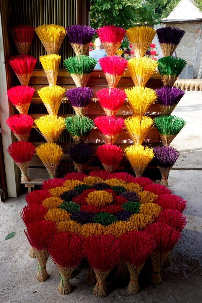 Bunte Räucher Stäbe stehen wie Blumensträuße angebunden da. Sie sind im Vordergrund im Kreis angelegt. Rot, Gelb, Blau, Rot und Gelb. Dahinter stehen die Räucher Stäbe in 6 Reihen mit jeweils fünf Bündel. Die Farben sind Rot, Gelb, Blau und Grün, Rot, Gelb und Blau und Grün.