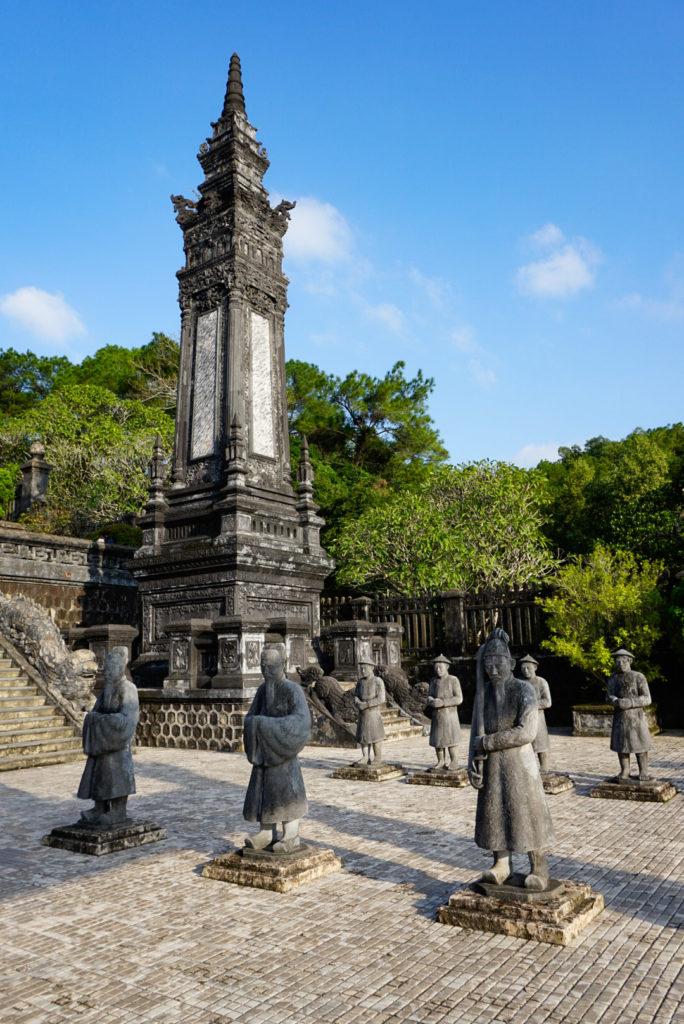 In einem Tempel der aus Beton besteht und daher sehr alt wirkt, stehen 5 Figuren. Diese stellen hohe Regierungsbeamte und Bauern dar.