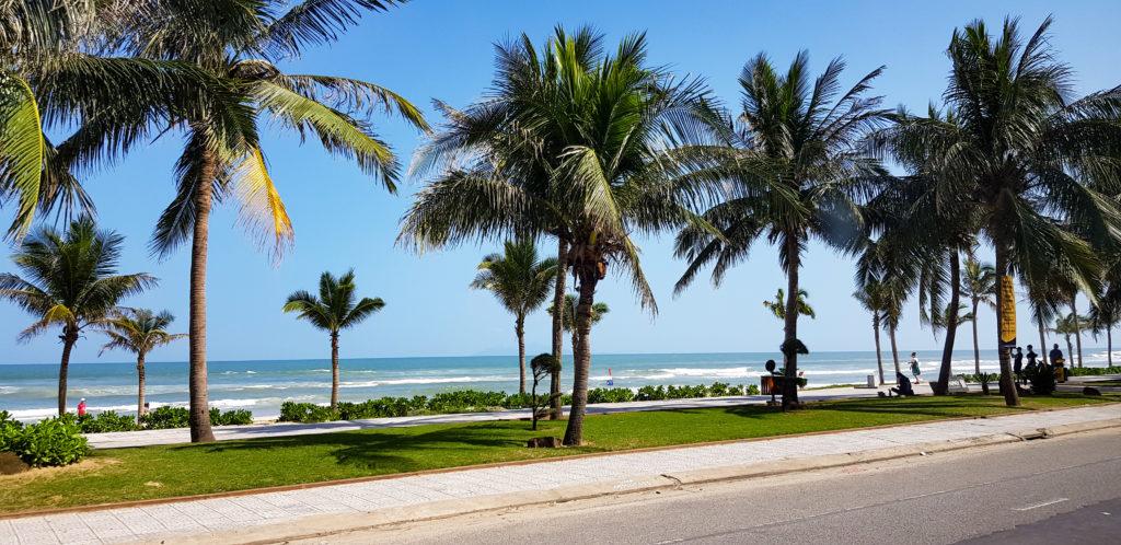 Eine Strandpromenade in Da Nang. Zwischen der Straße und dem Gehweg sowie dem Strand ist ein Grünstreifen mit Palmen. Dahinter säumt sich das Wasser.