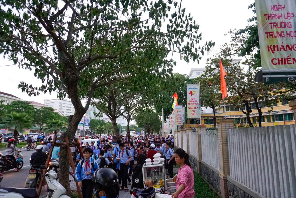 Schulschluss in Zentralvietnam. Hunderte von Schülern drängen sich auf dem engen Weg. Die Schüler werden per Moped von ihren Eltern abgeholt, dadurch ist es noch enger.