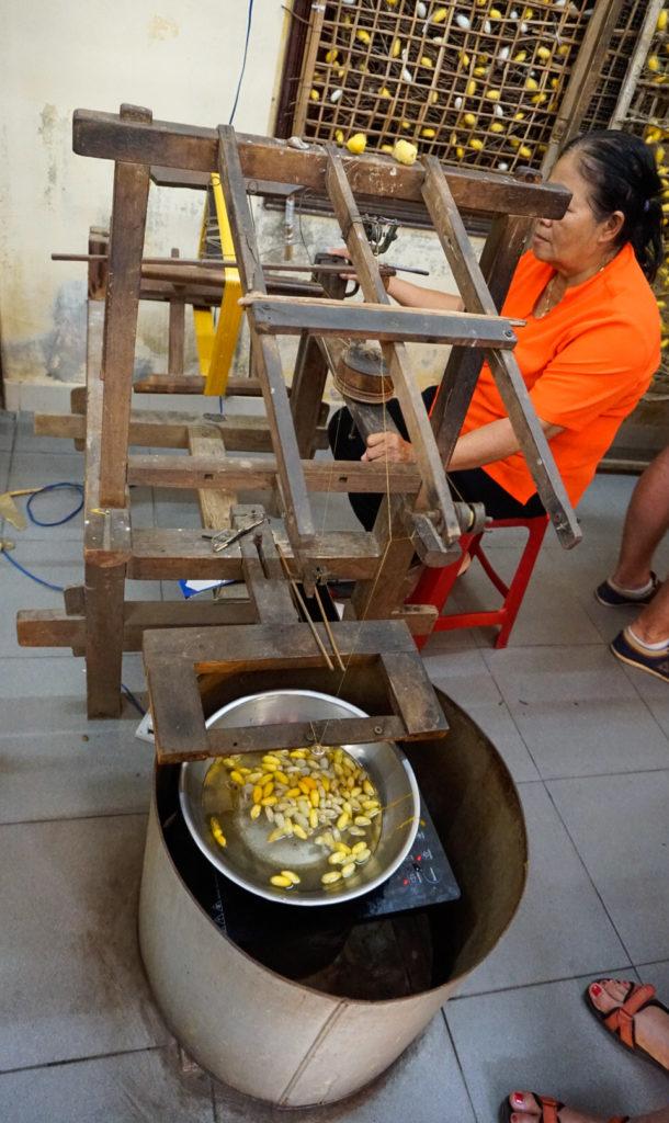 Eine Frau sitzt an einem Gerät zur Herstellung von Seide. Das Holzgerät zieht die Fäden von Raupen, die davor in einem Wasserbehälter liegen.