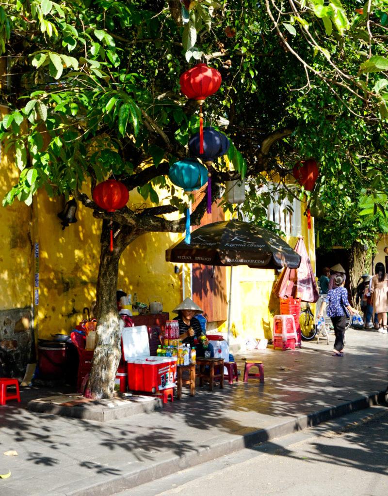 Eine Gasse in Hoi An. Am Baum hängen Lampions. Vor einem gelben Haus im Hintergrund sitzt eine Frau und verkauft Getränke und Speisen.