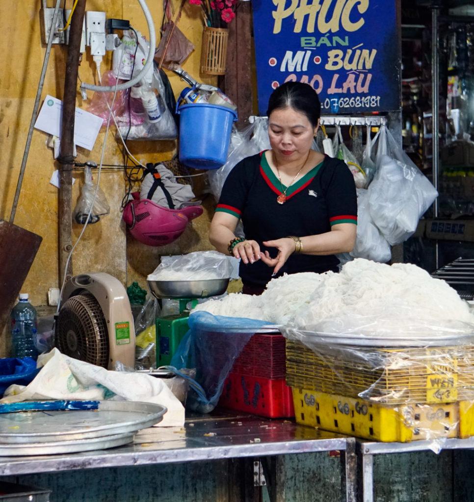 Eine Frau verpackt an einem Marktstand Reisnudeln in Tüten. Die Reisnudeln können auf den Gramm gekauft werden.